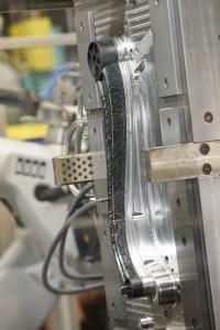 Das neue Langfaser-Direktspritzgießen präsentierte Arburg auf der K 2013 mit dem Umspritzen eines endlosfaserverstärkten Thermoplast-Einlegers (Tepex-Organoblech). In 40 s wurde ein über 500 mm langer und nur 200 g schwerer hochfester Composite-Hebel gefertigt. (Foto: Arburg)