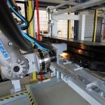 """Roboter im Arbeitsprozess """"Bolzen kleben"""", Bauteil wird an der Bolzenposition erwärmt. (Foto: Reis)"""