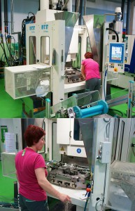 Abb.5a+b: Großserien-Produktionszelle für TPE-Faltenbälge mit je zwei umspritzten Anschluss-Stücken aus PA-GF, bestehend aus einer LWB C-Rahmen-Maschine vom Typ VCKM 1000/380 mit 1200 mm Rundtisch und Thermoplast-Spritzeinheit. Die Entformung der Faltenbalg-Rohre aus TPE erfolgt in diesem Fall automatisch, das Einlegen der PA-Teile manuell. (Fotos: Bauer)