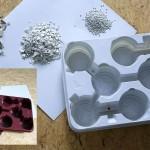 """Die Prozesskette im PS-Recyclingkonzept von CPE: Vom angelieferten groben PS-Mahlgut aus Kühlschrank-Innenbauteilen mit großen Anteilen an Fremdstoffen (oben links) über das gereinigte Mahlgut in sortierter """"Weiß-Qualität"""" (Mitte) zum extrudierten PS-Granulat (rechts) – und aus dem Rezyklat hergestellte Folien sowie daraus thermogeformte Pflanzentrays. Kleines Bild: Die aus PS-Rezyklat entstehenden Mehrschichtfolien können eingefärbt werden, um Trays in unterschiedlicher Farbgebung herzustellen. (Foto: Ettlinger)"""