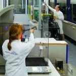 Genauigkeit, Zuverlässigkeit und eine ergonomische Bedienbarkeit waren Hauptmerkmale bei der Auslegung des Charpy Gerätes (Vordergrund). Mit mehr Funktionalität und Effizienz präsentiert sich die neue Arburg Spritzgießanlage im Labor (Hintergrund). (Foto: Polycomp)