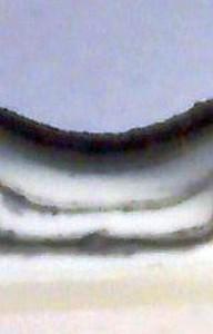 Mikroskopaufnahme eines Querschnitts durch den Bindenahtbereich eines Formteils, der zeigt, dass die Schmelze in der neuartigen Mischzone des Blaskopfes in mehrere Schichten aufgeteilt wird, die dann schließlich in der Bauteilwand wie bei einem coextrudierten Teil übereinanderliegen (Foto: Groß Kunststoff-Verfahrenstechnik)