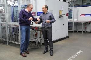 Michael Daigler, Geschäftsführer Daigler Kunststofftechnik (r.), erklärt Manfred Nerz, Vertrieb Wittmann Battenfeld, das mit der MacroPower hergestellte Teil. (Foto: Wittmann)