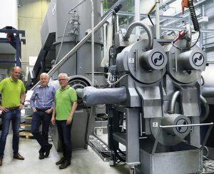 Stefan Kaiser (Vecoplan), Clemens Kitzberger (Erema) und Michael Hofmann (FVH) vor der Intarema 2021 TVEplus im Recyclingwerk der FVH in Schwerin. (Foto: Erema)