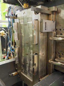 Es werde Licht: Hier wird ein Werkzeug, in diesem Fall mit einem Flachklinkenzug, auf einer der internen Spritzgießmaschinen abgemustert. Die Länge des fertigen Bauteils, eines Lichtleiters, beträgt 1,10 m. (Foto: Strack Norma)