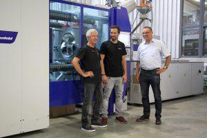 v.l.n.r.: Joachim Fröbel und Sohn Tobias Fröbel mit Erwin Neugebauer von Wittmann Battenfeld vor der MacroPower Combimould. (Foto: Wittmann Battenfeld)