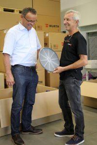 Joachim Fröbel zeigt Erwin Neugebauer von Wittmann Battenfeld den auf der 2-Komponenten MacroPower gefertigten Boden für einen Hocker. (Foto: Wittmann Battenfeld)