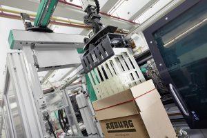 Raffinierte Turnkey-Lösung: Der Multilift V 40 magaziniert die Spritzteile in eine Zwischenablage und übernimmt – sobald sieben Gehäuse fertig sind – das integrierte Kartonieren. (Foto: Arburg)