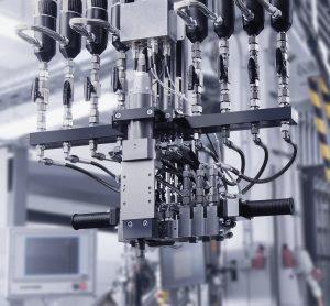 Das speziell für Votteler konzipierte Beschichtungssystem verfügt über einen Mischkopf für vier Komponenten. Daher können neben den beiden Lack-Grundbestandteilen, transparentes Polyol und Isocyanat, zwei weitere Komponenten zudosiert werden. (Foto: Votteler)