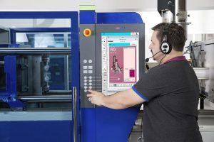Bediener bei der Vornahme von Roboter-Einstellungen über die Steuerung der Spritzgießmaschine Unilog B8. (Foto: Wittmann)
