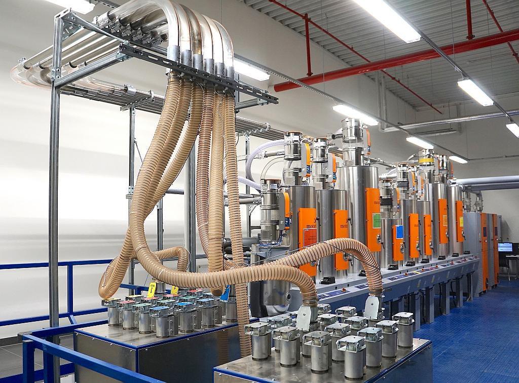 Manuell zu bedienender Kupplungsbahnhof zur flexiblen Versorgung der Verarbeitungsmaschinen mit getrocknetem Kunststoffgranulat. Die Verwechslungssicherheit wird dabei durch Farb-Codierungen der Kupplungsstücke und elektronische Codierstecker unterstützt. (Foto: Reinhard Bauer)