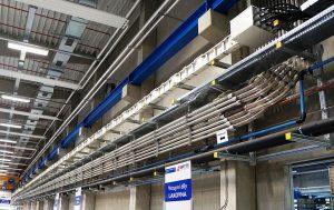 Die Materialleitung zwischen Trocknungsanlage und den Spritzgießmaschinen, bestehend aus Edelstahlrohren und Glas-Rohrbögen. (Foto: Reinhard Bauer)