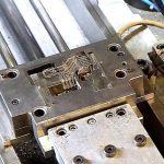 Komplexe 3-dimensional geformte Leiterbahnstrukturen werden direkt aus der Stanz-/Biege-anlage von einem Roboter an die Rundtischmaschine übergeben. (Foto: Reinhard Bauer)