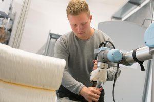 Moritz Wesseler stattet den Roboterarm mit einem Extruder aus. (Foto: FH Münster)