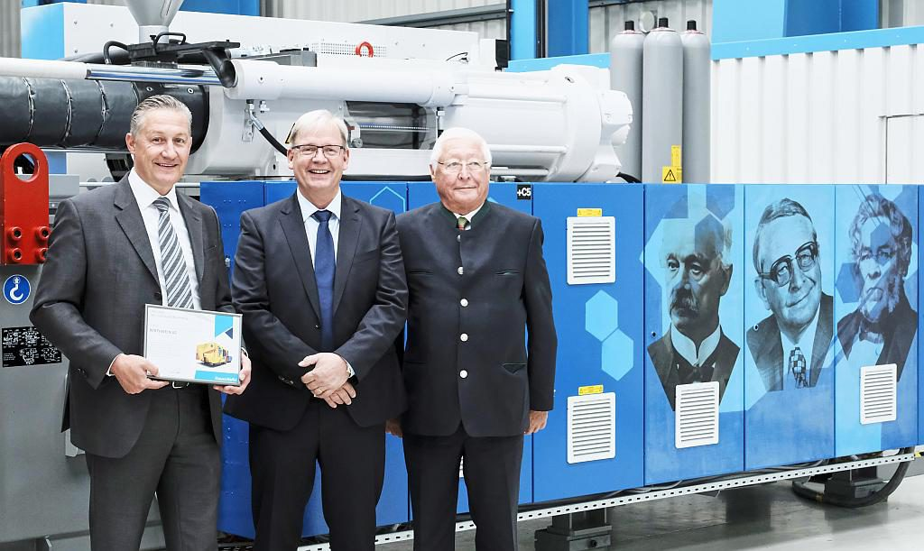 Tradition und Moderne vereint: Marcus Wirthwein, Dr. Hans Ulrich Golz und Udo Wirthwein vor der Jubiläumsmaschine. (Foto: KraussMaffei)