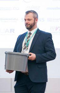 Christoph Burgstaller, Leiter des Projekts und Geschäftsführer des außeruniversitären Kunststoff-Forschungsinstitutes Transfercenter für Kunststofftechnik in Wels, mit einer Vorstudie des Speiseöl-Sammelbehälters Öli aus 100 % Recyclingmaterial. (Foto: Biz-Up)
