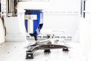 Führt ein Werker der Maschine ein endkonturnah hergestelltes CFK-Bauteil zu, fräst sie es zunächst hochpräzise. (Foto: Fraunhofer IPA/Rainer Bez)