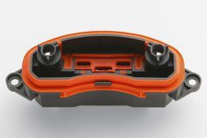 Steckergehäuse mit aufgespritzter orangefarbiger Radialdichtung aus Elastosil LR 3675. Der selbsthaftende Flüssigsiliconkautschuk besitzt eine gleitfähige Oberfläche und lässt sich folglich gut montieren. (Foto: Wacker)