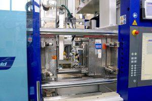 Beide Spritzgießmaschinen sind mit Rolle-zu-Rolle-Folienvorschubeinheiten ausgerüstet. Die Roboter tragen eine Folien-Wärmeplatte und gegenüber davon den Sauggreifer zur Fertigteil-Entnahme. (Foto: Reinhard Bauer)
