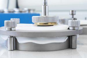 Abrasionstest eines Kunststoffteils aus TPU, das mit Genioplast Pellet 345 modifiziert wurde. Das neue Siliconadditiv verleiht solchen Oberflächen eine höhere Glätte und verbessert ihre Kratz- und Abriebfestigkeit. (Foto: Wacker)