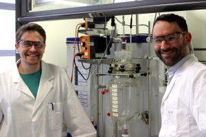 Paul Stockmann und Dr. Van Opdenbosch mit dem Reaktor, in dem das polymerisationsfähigen Monomer aus dem Naturstoff 3-Caren hergestellt wurde. (Foto: C. Zollfrank / TUM)