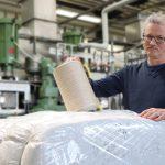 Dr. Frank Wendler mit Material der Marke Cell Solution bioactive – einmal eine Spule mit einem Endlosfaden, darunter versandfertig verpackte Stapelfasern. (Foto: smartpolymer/Steffen Beikirch)