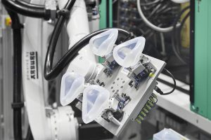 Pro Zyklus entstehen vier LSR-Masken, die von einem Sechs-Achs-Roboter entnommen werden. Pro Tag können rund 3.500 der multifunktionalen Hightech-Masken produziert werden. (Foto: Arburg)