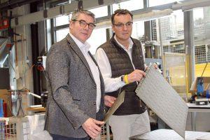 Dirk Wevelsiep zeigt Thomas Bertram die neue Produktentwicklung, eine Bodenplatte mit selbstabdichtendem Hinterschnitt. (Foto: Wittmann Battenfeld)