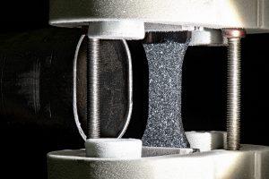 Eine trockene Kunststoffprobe vor der Düse, die Einspannung ist vereist. (Foto: Fraunhofer LBF)