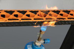 Brandtest an einem Modellträger aus einem der neuen Tepex-Typen sowie der Verrippung aus einem orangenen, halogenfrei flammgeschützten PA 6. Die Flammen breiten sich nicht aus, sondern verlöschen nach Entfernen des Brenners. (Foto: Lanxess)