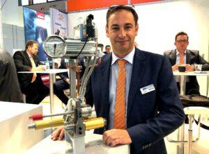 Christian Stiegel, Geschäftsleitung Technik und Produktion bei Incoe, zeigt das Direct-Flo-Heißkanalsystem mit Heat-Inject-Einheit. (Foto: K-AKTUELL.de)